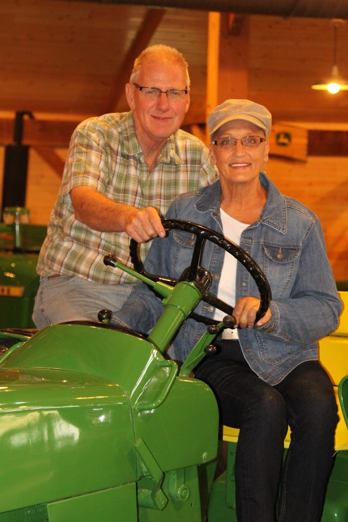 husband and wife, owners of barn, posing for a photo on tractor