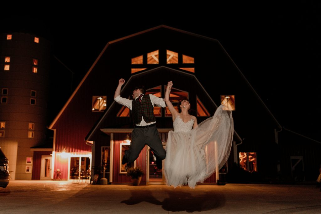 bride and groom jumping with excitement in front of barn at night