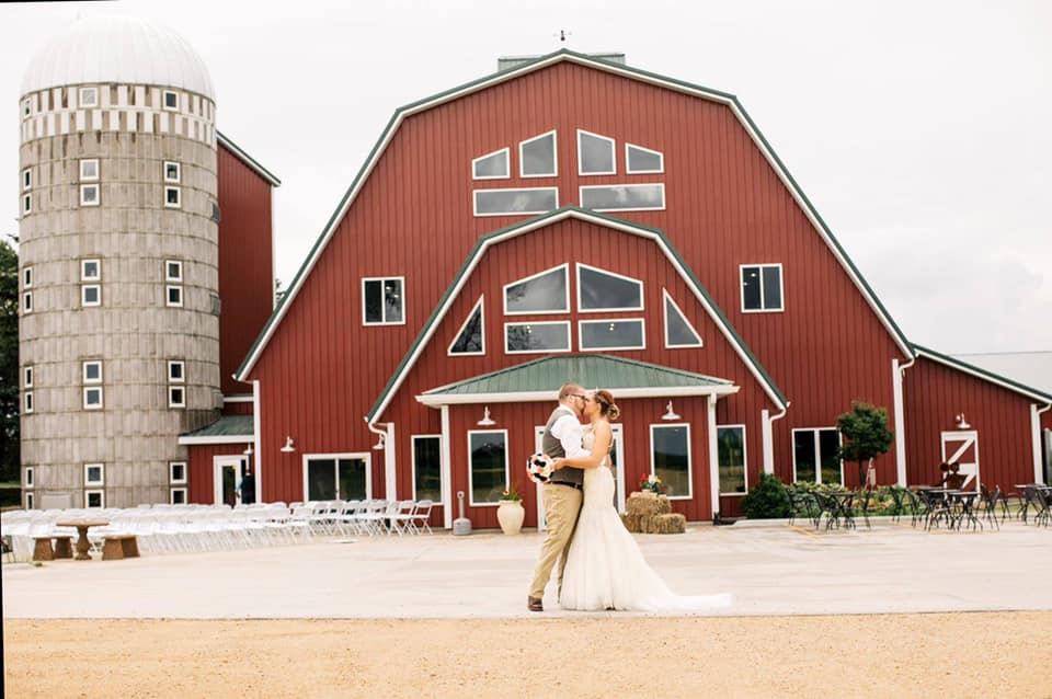 bride and groom in front of large red barn and silo